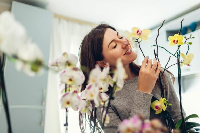 Woman Smelling Orchids
